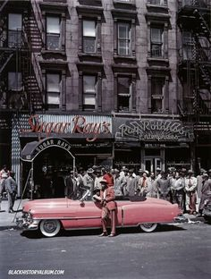Boxer Sugar Ray Robinson styling in front of his flamingo-pink Cadillac. In the background……his night club and eatery, Sugar Rays, 1950. © George Karger, Life Magazine