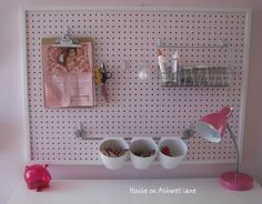 I really like the versatility of pegboards.  And I really like the how serene the color scheme on this one is.  Though, for me personally, I think I would switch out the pink for a blue.