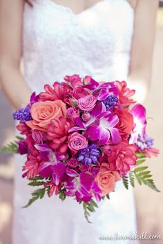 Wedding bouquet of vivid roses, orchids, pink ginger, with periwinkle accents.