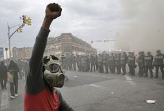 "From Funeral to Riot: 7 Hours In Baltimore. Two police cars, a cruiser and a transport van, were on fire at the intersection of Baltimore's North and Pennsylvania Avenues. Dozens of people poured out of a CVS on the same corner, arms full of toilet paper and baby wipes. An older man in a pageboy cap put his hand on my shoulder and walked with me for a few steps. ""You've gotta get out of here,"" he said. ""These people are crazy. They want to hurt people who look like you."""