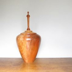 Cherry wood has been turned and hollowed to form this urn. Entire piece has a warm tawny color. Fine brown grain lines are visible throughout