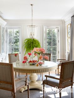 A light and airy breakfast room, with pale gray Regency armchairs by Noir gathered around Hickory Chair's Gustav table. Zurich lantern by Vaughan. Design: Michael S. Smith