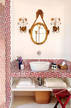 Red tiled bathroom with deep porcelain sink. Gold mirror and gold wall sconces. #wallsconce #redtiles #goldmirror Lazy Sunday - DustJacket Attic