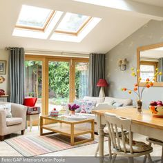 Gemütlich und heimelig wirkt die Wohnzimmereinrichtung. Der Landhausstil für das Wohnzimmer wird besonders mithilfe von hellen Holzmöbeln in Weiß und Hellbraun geschaffen. Umnterstützt wird dies vor allem durch den Esstisch, aber auch durch den Couchtisch und die Terrassentür in Kombination mit der weißen Wand. Damit der Raum nicht zu schlicht wirkt, sorgen farbige Accessoires, wie der gestreifte Teppich, Blumen und die Sofakissen, für eine dezente Akzentuierung.