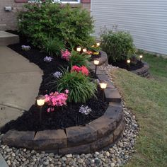 Rock retaining wall, premium mulch, rocks, and low voltage lighting