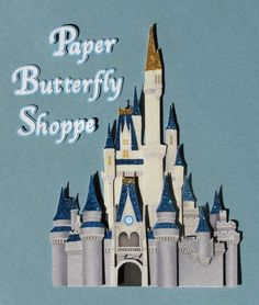 This hand crafted embellishment is designed after Cinderellas castle in Walt Disney world. It measures 4.5 x 6.25 inches and is made from printed card stock. The tower tops are decorated with blue and gold glitter and the paper is layered to give the castle dimension. Use it to