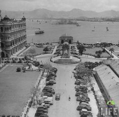 """The view from the old HK Bank building in 1948 ~ """"Statue Square"""" (皇后像廣場 lit Queen Statue Square), Central. The statue was intended to be made from marble but by error (some kind of), it ended up in bronze. During Japanese occupation in WWII, the statue, along with many more including the lions at HSBC were displaced. All sides of the canopy was sealed. After the War, most of the statues were recovered. The Queen statue was relocated to Victoria Park in Causeway Bay."""
