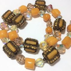 Mid Century lucite and aurora borealis glass bead necklace Butterscotch lucite beads are wrapped in golden prong set rhinestones and copper colored glass seed beads Faceted aurora borealis glass beads Gold tone pin clasp 22 inches long Wrapped beads are 5/8 inches square Very good