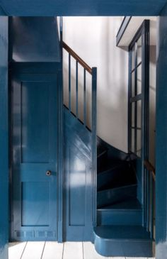dark teal entryway and staircase with painted white wood floors. #wallpaint #tealpaint #bluepaint #bluewalls #bluestairs #entryway #staircase