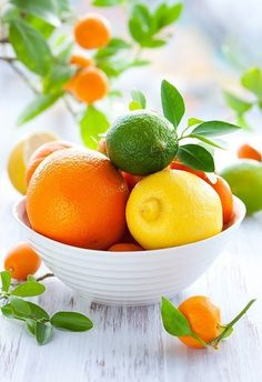 white bowl filled with orange lemon and limea