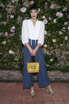Mia Moretti in a white Rebecca Taylor top and wide-leg trousers, yellow Roger Vivier bag, Salvatore Ferragamo platforms with colorful sole.