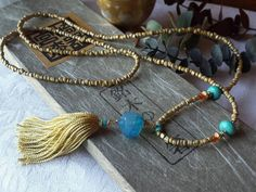 A soft blue faceted Agate nugget hangs from this long Mala Style Necklace. I added Chalk Turquoise and Tangerine Jade as accents. The length of the necklace is made of pebble beads in a sandy slightly pearly color that gives off golden light. I hung a Satiny Aztec GoldTassel below. Your
