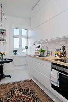 witte strakke keuken, warm werkblad, ouderwets tapijt en een leuk raam.