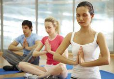 Unge mennesker mediterer på yogamatter