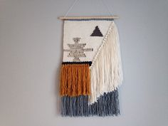 This neutral toned hand-woven wall hanging measures 21 in length (from dowel to fringe) and 12 across, hung on a 12 long wooden dowel.  Made using