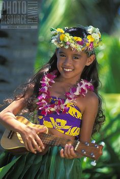 Beautiful Hawaiian girl (age 7) playing ukulele with orchid lei, haku lei on head and ti leaf skirt