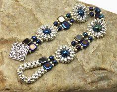 Un design unique superduo qui donne l'illusion d'une spirale en incorporant des deux couleurs de Superduos en spirale autour de la perle du milieu. Ce bracelet utilise argent mat et superduos gunmetal ou l'hématite perlés dans un motif floral en spirale autour d'un verre tchèque gris foncé nacré. Miyuki duracoat galvanisé étain clair, perles de rocaille ont été utilisés comme un embellissement. Le fermoir est une boucle de perles qui glisse sur un bouton plaqué JBB argenté avec un motif…