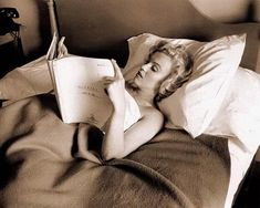 Marilyn Monroe gets comfortable and reads.