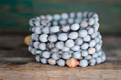 bracelets made in uganda from embira seeds, and peppered with colorful beads made of paper.     Very fun to wear. Makes great gift