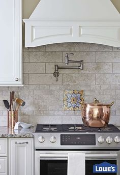 Your kitchen workspace should offer convenience and character. A pot-filler and cabinet-covered hood complement a stylish backsplash treatment in this designer kitchen.