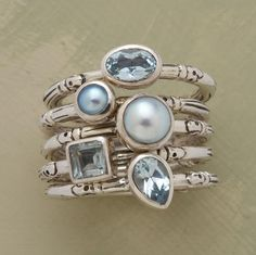 A finger full of pale blue gems, all bezel set on sterling silver bands. Three of the rings bear faceted cuts of topaz, two uphold blue cultured pearls.
