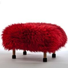 This fleece is from the rare Dragon Sheep which roam wild in the volcanoes of Snowdonia. #MightNotBeTrue ...Nia in Dragon Red. A luxury sheepskin footstool handmade in beautiful North Wales, with a removable quirky Dragon Red coloured real British sheepskin cover.