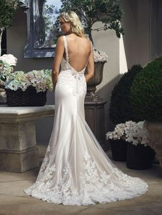 Style 2210 by Casablanca Bridal. Sheath silhouette gown made of Luxe Silky Charmeuse with non-beaded lace appliqués on tulle that embellish the bodice and the skirt. Gown features tank straps that have an organic lace edge that goes along the front and back V-necklines. Small of waist is accented with a petite band. Low V-back neckline has a sheer panel of lace.