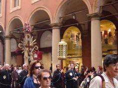 Sbucate su via Saragozza, ma il marciapiede è ingombro di fedeli che attendono la discesa della Madonna di San Luca. Di fronte alla vetrina di Sandra, la parrucchiera, due donne con i bigodini in testa e l'asciugamano a mo' di stola, attendono la benedizione della Vergine prima di tornare a quella della messimpiega. Madonna, Street View