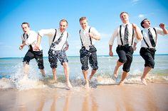 REAL DOOR COUNTY WEDDING. Photo by GreatScott Images. Groomsmen run through the waves. Location: Lake Michigan, Door County Wedding, Wisconsin