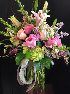 Lilacs, garden roses, hydrangeas, lilies, orchids and snapdragons arranged in a tall vase.