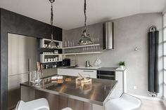 This Attic Apartment's Design Makes It A European Penthouse #refinery29  http://www.refinery29.com/design-milk/10#slide-13  Stainless steel is used for the island and for the appliances helping to reflect light in the space. They also went with open shelving to make the kitchen appear more open.   ...