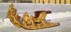 Fanciful Viennese baroque sled, 1725-1789. The sculpted, clamshell-shaped, wooden body, is fixed firmly on skids fully gold plated (in Museum Wagenburg - a museum of carriages and vehicles used by the imperial household of the Austrian Empire). In 17th century Vienna 'race sledding' parades were special events. The imperial family & the nobility paraded through the main sites of the city. All were dressed in their finery. (4th of four pins)