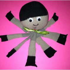 Socktopus #craft for #kids. So easy! Cut a sock in half at the heel. Put fiber fill in the toes part of the sock and then tie closed with a rubber band. Cut the bottom into 8 legs then add google eyes and draw on the mouth with Sharpie. Tie on a bow and you're done!