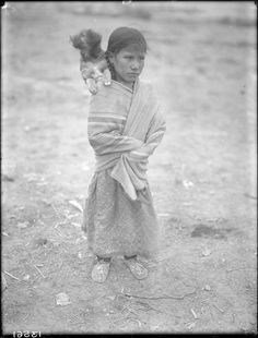 A Cheyenne girl carrying a dog on her shoulder. 1910.