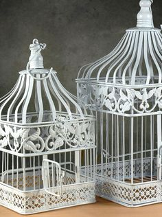 "Set of 2 white metal birdcages.  Use one for holding cards at entrance table; other for dessert table.  Large is 17.5"" tall x 9"" square; small is 13.5"" x 7"".  Top lids are hinged, lift off for easy card removal; front door opens w/ built-in latch.  Comes w/ hook for hanging.  $22 for both."