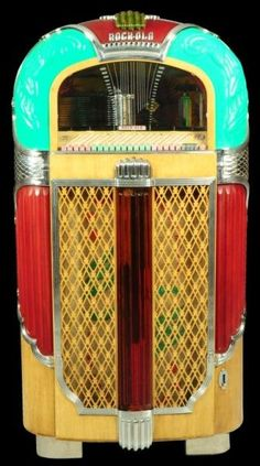 """1948 Rock-Ola Jukebox, the model 1428 jukebox was the third and last of the """"Magic-Glo"""" series of jukeboxes that Rock-Ola produced as competition to Wurlitzer's post-war production line. Its art deco styling, strong colors and color animation made it one of the most attactive jukeboxes in all of time. It featured deep colored red and green cabinet plastics, and """"animation"""" in ther form of a revolving color cylinder. It plays a selection of twenty 78 r.p.m. records - opening bid USD 2,000"""