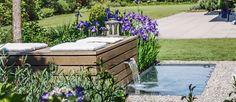 Lebendige Staudenbepflanzung mit Gräsern und ein Wasserspiel, das auch eine Sitzgelegenheit ist. Dieser Sitzplatz am Zürichsee ist ein kleines Juwel.