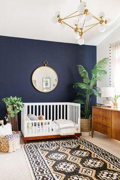 Deep navy wall with a boho rug and toddler crib