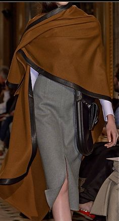 Hermès, Fall 2013: Flowing cape in tobacco colored cashmere with leather trim over a crisp white shirt; greige pencil skirt; large bandolier with attached pochette ~ Hermès Paris