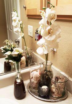 chattycrafting.com | Here's an updated photo of my beach themed bathroom idea on a tight budget. I think this would be great as apartment/small bathroom decor if you're not into nautical themes, but if you're more of a coastal decorator like me. I like this spa-like vibe. Dollar tree silver tray, seashell vase fillers, river rocks... #dollartree #bathroom #decor 5h