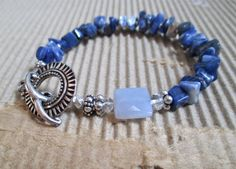Wrap your wrist with this bluesy duo of sodalite chips and a solo square, faceted chalcedony with a faceted quartz rondelle on either side with a