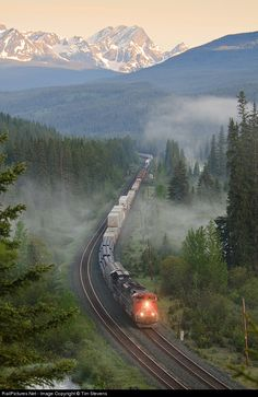 RailPictures.Net Photo: CN 8938 Canadian National Railway EMD SD70M-2 at Jasper, Alberta, Canada by Tim Stevens. CN A416 heads through some foggy swamps west of Jasper as the sunrise hits the mountain peaks..  Picture Puzzle perfect.