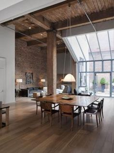 Great exposed wood ceiling, center beam, center piece lighting, exposed brick wall, wood flooring. by guida