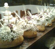 centro de mesa en pieza de pan, con flores, uvas y espigas.