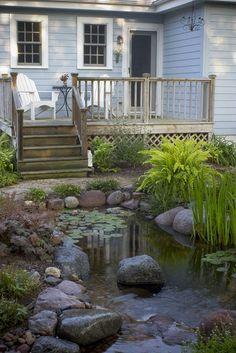 Small deck with backyard pond.