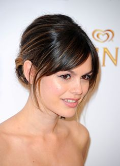 rich brown hair with carmel highlights. swooping bangs and slight face framing layers.