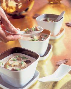 Pureer de soep met de staafmixer of in een keukenmachine. Roer de kookroom en de gebakken paddestoelen erdoor en verwarm de soep. Voeg peper en zout naar smaak toe en bestrooi de soep met het loof van de lente/bosuitjes.