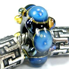 Black Large Hole Bead With Blue Trapped Air Bubbles and Raised Aurae Dots lhb064siblutabraud Handmade Lampwork Glass Bead, Slider Bracelet Bead This gorgeous beauty is one of my large hole handmade lampwork glass slider bracelet or necklace beads. It has a black base with bright blue raised dots that have trapped air bubbles around the center of the bead. I added raised silver rich Double Helix Aurae dots around both sides giving them an oil slick metallic sheen. The metallic sheen was diffi...
