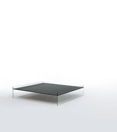 PONTE design Piero Lissoni, Marc Krusin, Carlo Tamborini | Low tables in tempered mm. 10 thick extralight glass. The top in glossy lacquered glass is supported by two transparent sides thanks to a special gluing on the thickness of the glass, obtaining this way a suspended effect. Available in two square sizes.
