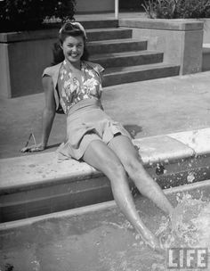 Esther Williams sitting by pool